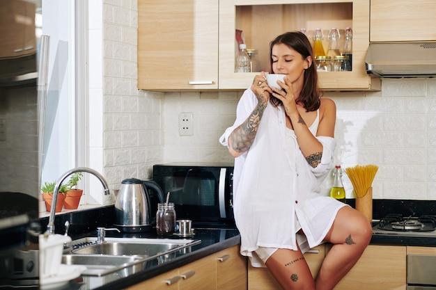 Atrtaktive junge frau, die auf küchentheke sitzt und köstlichen geruch von frischem kaffee genießt, den sie machte