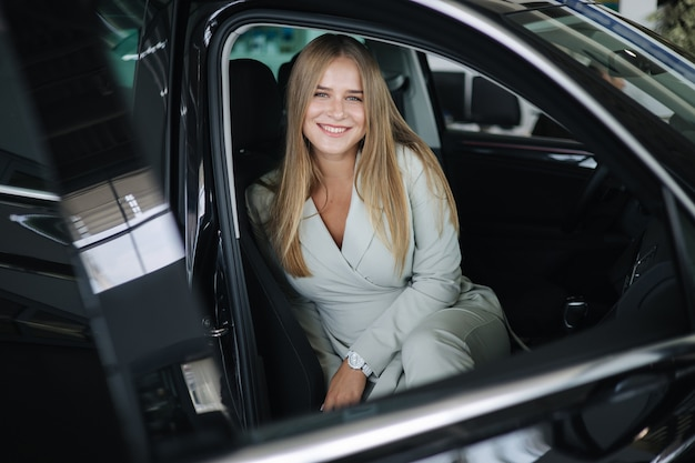 Attaktive junge geschäftsfrau, die im auto im autohaus sitzt frau, die neues auto schöne blondine wählt