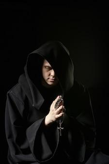 Attentäter in dunkler kleidung in der kirche. zauberer im schwarzen mantel, der mysteriösen ritus im dunklen raum tut. mönch betet in der dunkelheit. magisches ritual im schatten. sünder in schwarzer kapuze bereuen im schatten. mystery man.