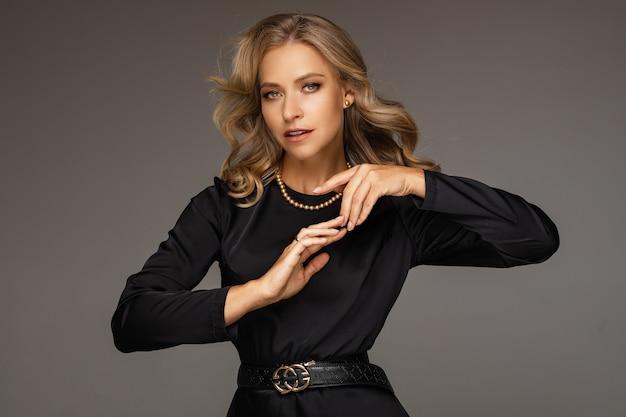 Attracrive kaukasische frau mit blonden haaren im schwarzen anzug auf grauem hintergrund isoliert