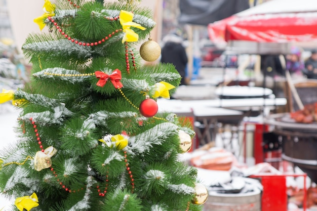 Attraktiv dekorierter weihnachtsbaum mit kugeln und bändern auf dem straßenmarkt hautnah
