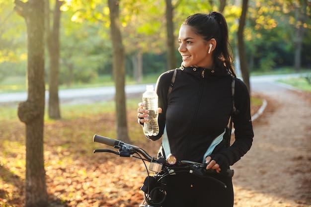 Attraktiv fit sportlerin mit fahrrad im park, trinkwasser aus einer flasche