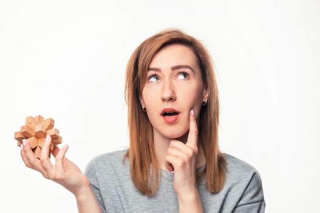 Attraktive 24-jährige geschäftsfrau, die mit hölzernem puzzlespiel verwechselt schaut.