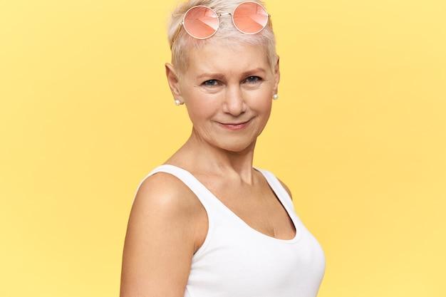 Attraktive 50-jährige europäische frau, die gegen gelben hintergrund mit kopierraum für ihre werbung aufwirft und stilvolle schatten auf ihrem kopf trägt. menschen, sommer, stil und modekonzept