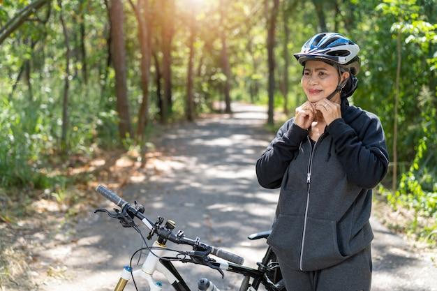 Attraktive ältere asiatische frau mit fahrrad im park