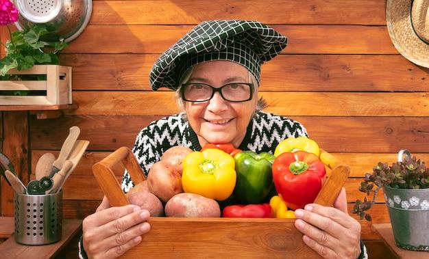 Attraktive ältere bäuerin hält einen holzkorb voller frisch gepflückter paprika und kartoffeln aus dem garten
