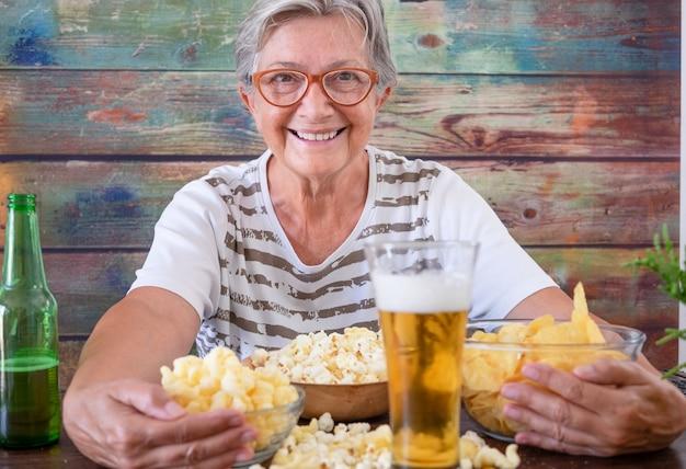 Attraktive ältere frau, die an einem holztisch mit bier und vorspeise sitzt und lächelnd in die kamera schaut
