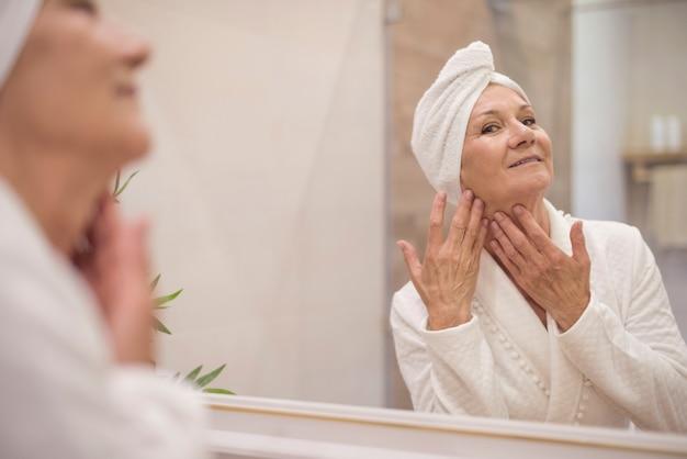 Attraktive ältere frau, die im spiegel stöbert