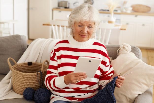 Attraktive ältere frau im roten weißen sweatshirt, das sich drinnen entspannt, auf sofa mit garn und nadeln sitzt, strickt, digitales tablet für online-shopping verwendet. ältere menschen, ruhestand, moderne technologie