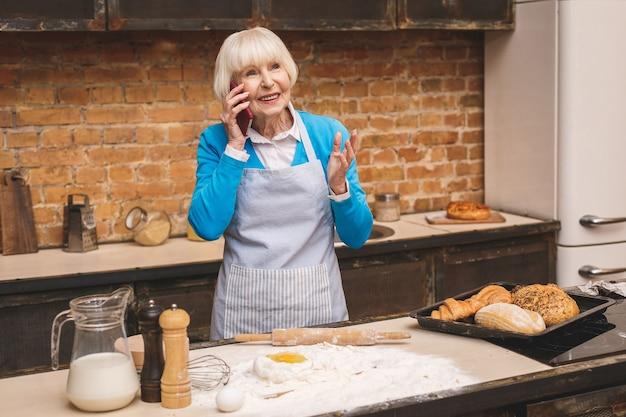 Attraktive ältere frau kocht auf küche. großmutter macht leckeres backen. telefon benutzen.