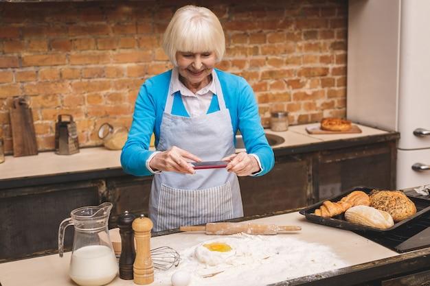 Attraktive ältere frau kocht auf küche. großmutter macht leckeres backen. verwenden des telefons für ein foto von oben.