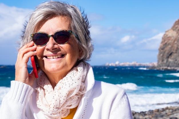 Attraktive ältere frau mit strandurlaub an einem windigen tag nutzt smartphone für einen anruf