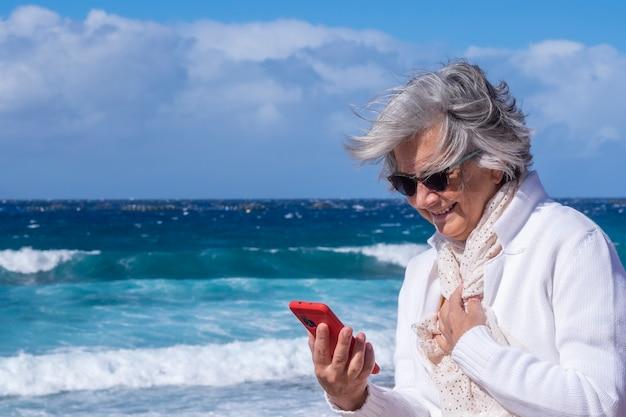 Attraktive ältere frau weiß gekleidet, die urlaub am meer an einem windigen tag mit smartphone genießt