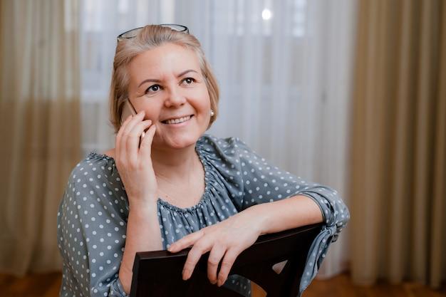 Attraktive ältere geschäftsfrau mit einem lächelnden mobiltelefon, als sie über videolink auf den bildschirm schaut