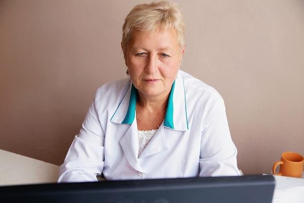 Attraktive ärztin, die an ihrem computer in ihrem büro arbeitet