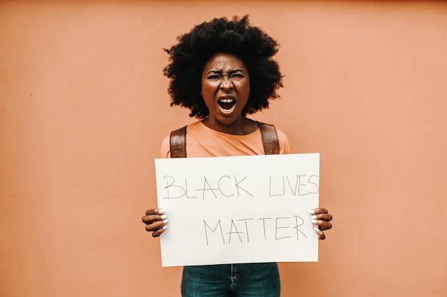 Attraktive afrikanische frau, die papier mit black lives matter hält! und schreien.
