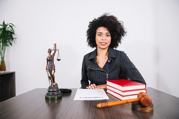 Attraktive afroamerikanerfrau bei tisch mit büchern, dokument und abbildung