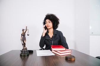 Attraktive Afroamerikanerfrau, die bei Tisch am Handy im Büro spricht