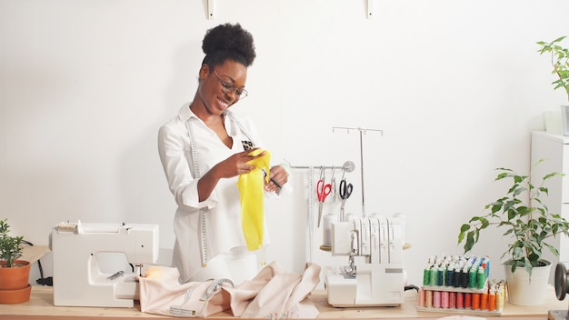 Attraktive afroamerikanische modedesignerin näht in ihrer werkstatt modische kleidung