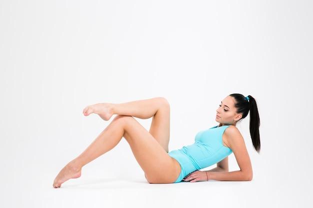 Attraktive akrobatenfrau, die beine auf dem boden lokalisiert auf einer weißen wand streckt