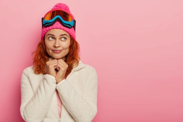 Attraktive aktive frau hat verträumten ausdruck, trägt rosa hut mit skibrille, kopierraum