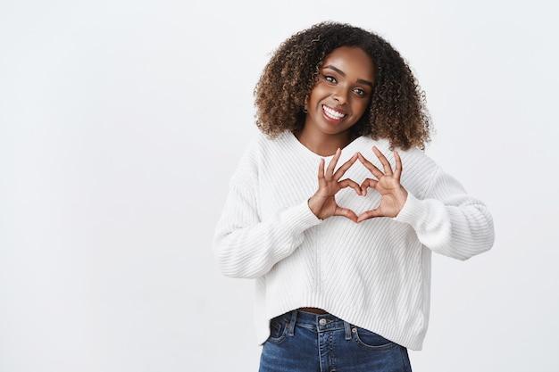 Attraktive alberne afroamerikanische frau afro-frisur zeigen herz geste neigung kopf lächelnd freudig ausdrücken sympathie leidenschaft romantische haltung, stehende weiße wand sorglos