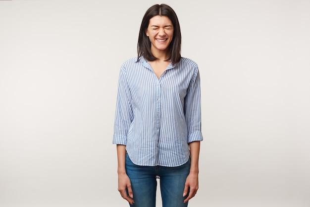 Attraktive angenehme junge dunkelhaarige frau in jeans und gestreiftem hemd, die auf eine unerwartete oder erstaunliche überraschung vom freund mit geschlossenen augen wartet, die über weißer wand isoliert werden