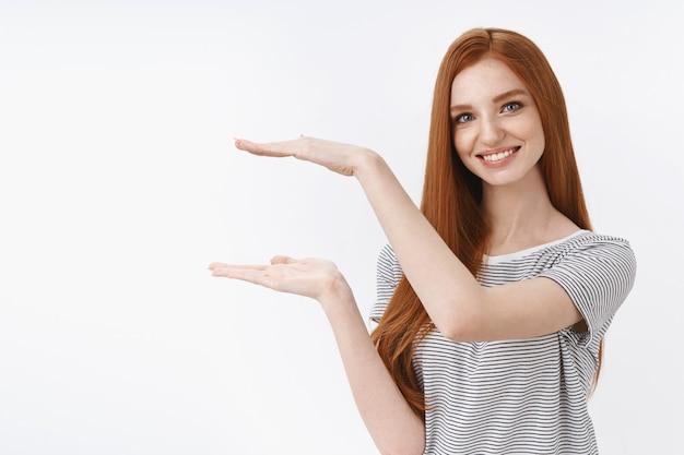 Attraktive, angenehme, selbstbewusste, fröhliche, lächelnde rothaarigefrau, blaue augen, die ein kleines objekt zeigen, heben die hände, die das produkt lächeln, das erfreut, guten service zu versprechen, an der weißen wand zu stehen