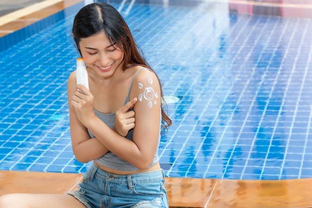 Attraktive asiatische frau, die eine flasche sonnencreme hält und sonnenschutz-sonnenschutz uv-schutz auf schulter aufträgt.