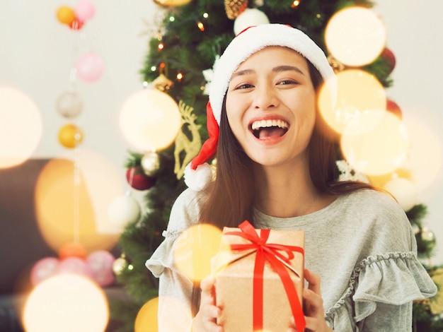Attraktive asiatische frau, die geschenkbox in den händen hält.