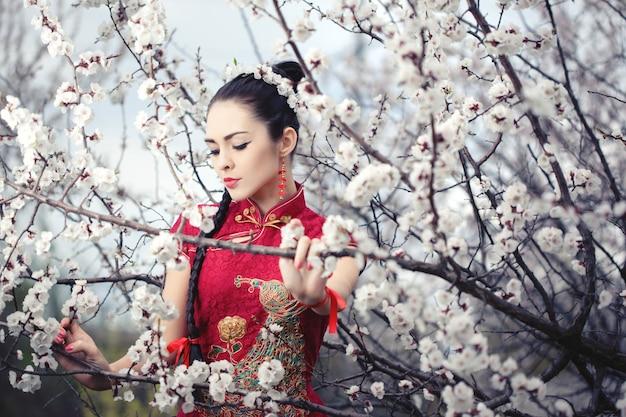 Attraktive asiatische frau, die kimono steht, der im blühenden garten steht.