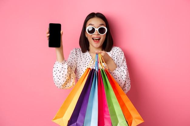 Attraktive asiatische frau, die smartphone-app und einkaufstaschen zeigt, die online über den anwendungsstand...