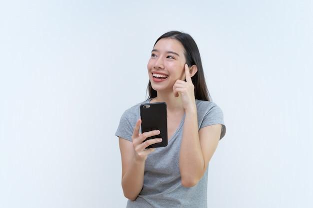 Attraktive asiatische frau, die smartphone und das denken hält