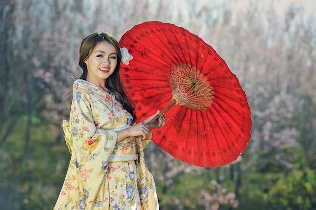 Attraktive asiatische frau, die traditionellen japanischen kimono mit rotem regenschirm trägt