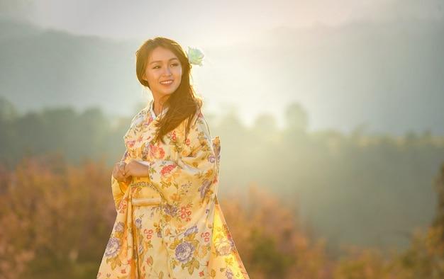 Attraktive asiatische frau, die traditionellen japanischen kimono trägt