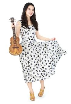 Attraktive asiatische frau, die ukulele spielt
