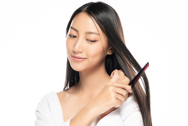 Attraktive asiatische frau, die um ihrem haar sich kümmert.