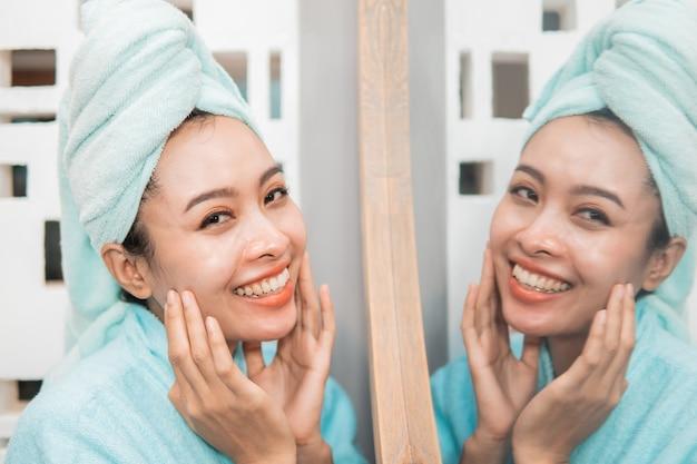 Attraktive asiatische frau, die vor spiegel mit handtuch am badezimmer steht
