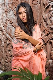 Attraktive asiatische frau im ethnischen boho-kleid, das über zierwand des holzes aufwirft.