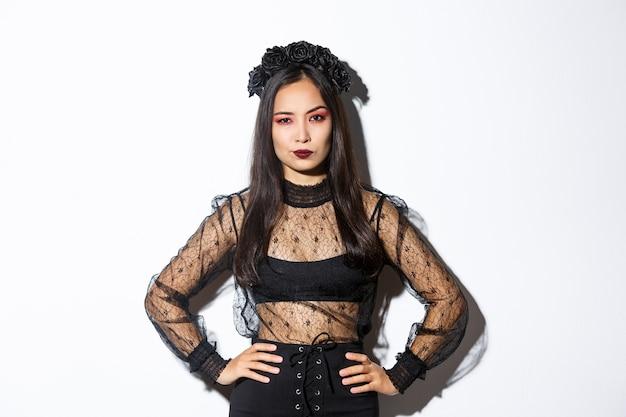 Attraktive asiatische frau im halloween-kostüm, die enttäuscht und skeptisch aussieht. frau im schwarzen spitzenkleid und im kranz, der arrogant aussieht, süßes oder saures im hexenoutfit, stehenden weißen hintergrund.