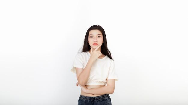Attraktive asiatische frau im stehenden denken des neutralen lässigen outfits
