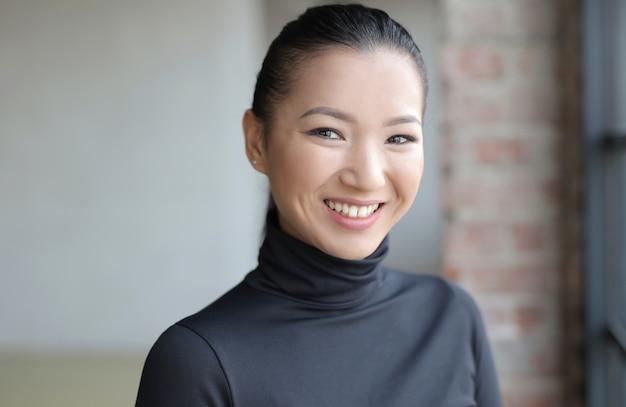 Attraktive asiatische frau in einem schwarzen outfit, das sanft lächelt