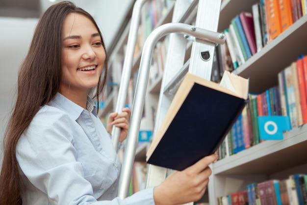 Attraktive asiatische frau lächelnd, ein buch an der bibliothek lesend