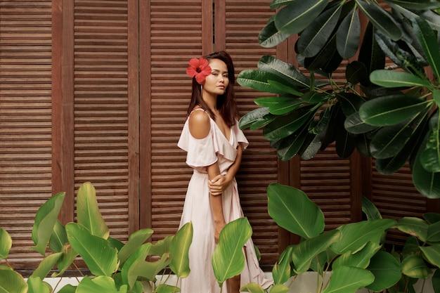 Attraktive asiatische frau mit hibiskusblume in den haaren, die im tropischen garten aufwerfen.