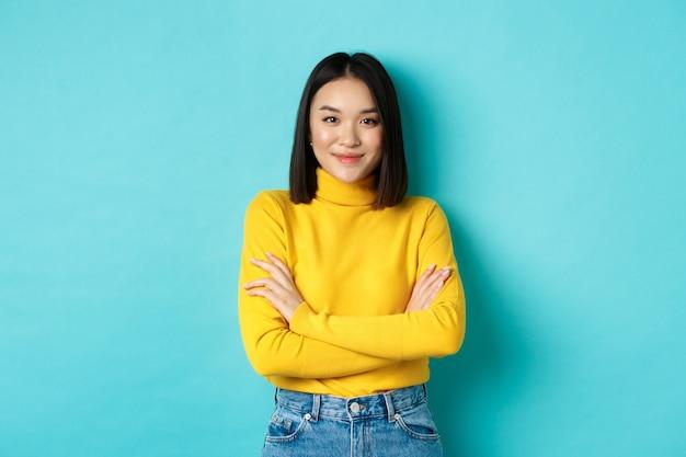 Attraktive asiatische frau mit kurzen dunklen haaren, verschränkten armen auf der brust und selbstbewusst lächelnd, über blauem hintergrund stehend