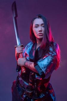Attraktive asiatische frau mit samurai-outfit mit katana vor neonfarbenem hintergrund.