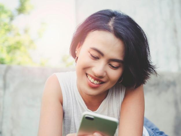 Attraktive asiatische frau mit schwarzen kurzen haaren im lässigen weißen ärmellosen hemd, die lächelt, während sie smartphone auf dem gebäude und grünem naturhintergrund verwendet.