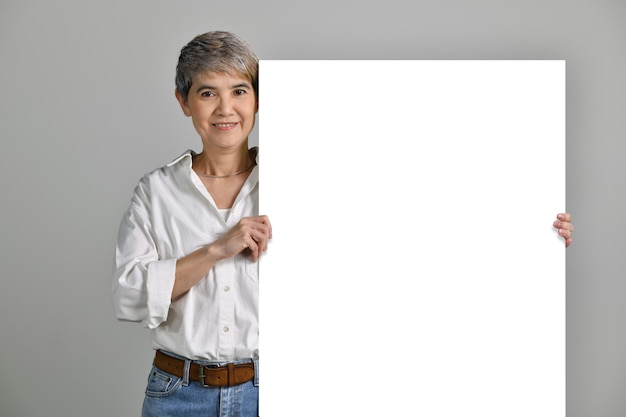 Attraktive asiatische frau mittleren alters, die leeres schild lokalisiert auf weißem hintergrund hält. in die kamera schauen