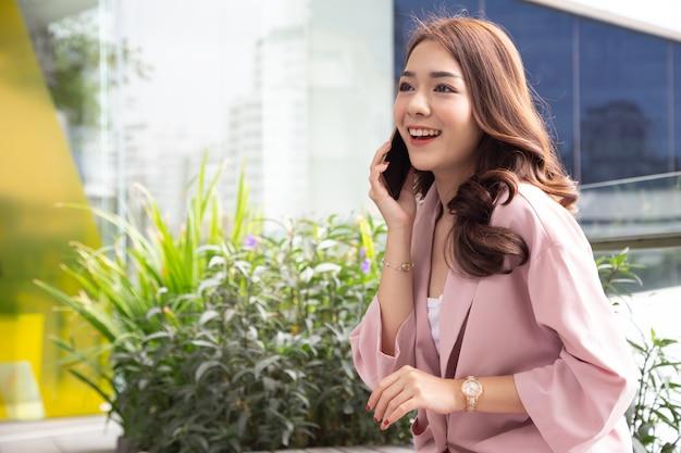Attraktive asiatische geschäftsfrau, die am handy mit kunden spricht