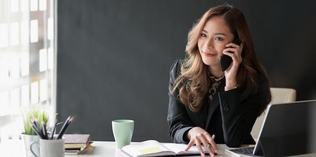 Attraktive asiatische geschäftsfrau, die am telefon mit kunden spricht